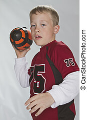 6 years old boy wearing a jersey and throwing a football