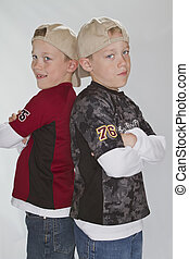 6 years old identical twins wearing a baseball hats
