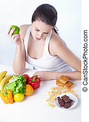 Healthy or unhealthy food - The girl looks for food on a...