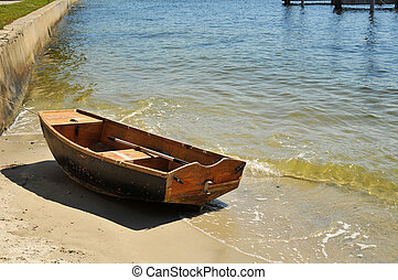 Small sailboat tied off againt a se - Small sailboat tied...