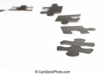 different black puzzle pieces over white background
