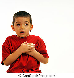 Alarmed boy with hands over heart, eyes open having been...