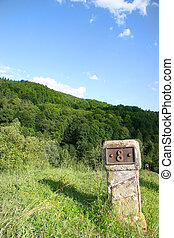 milestone marked with eight and positioneda on a hill