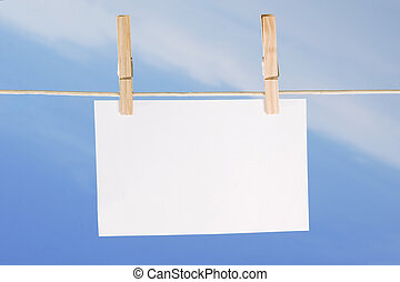 blank paper and clothes peg on blue sky background