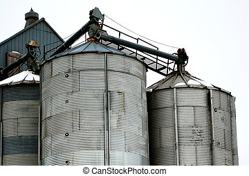 Grain Storage Bins in Winter - Three grain bins. The...