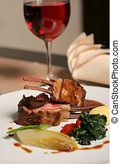 lamb meal and red wine - restaurant table with a plate of...