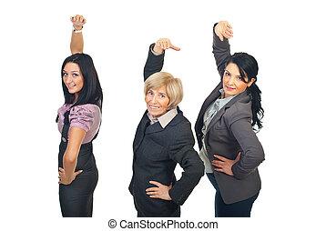 Team of businesswomen stretching hands - Team of three...