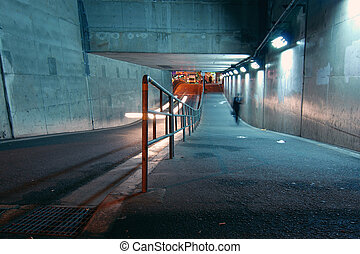 urban night - men walking in the underway tunnel at the...