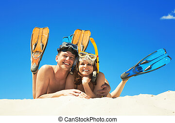 Leisure - Happy family with flippers lying on sand and...