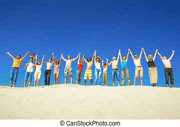Group during summer - Happy group holding by hands and...