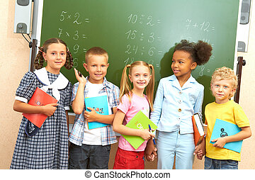 Classmates - Portrait of several kids standing by blackboard...