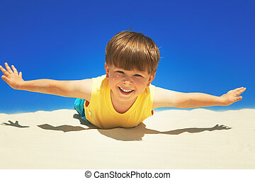 Joyful boy stretching his hands and lying sand