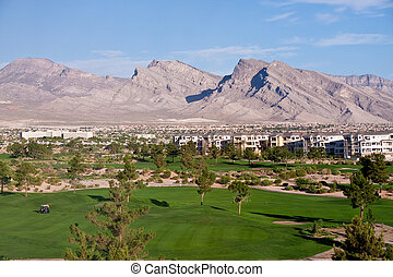 Golf Cart on Green of Desert Course by Mountains