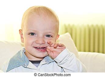 Kid biting his finger - Smiling caucasian child biting with...