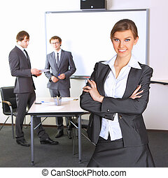 Portrait of business woman with team mates discussing in the background