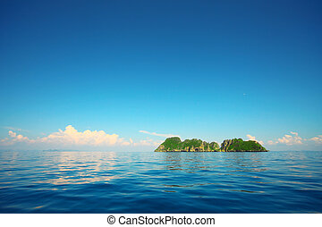 Island in sea - Tropical island in a blue sea and blue sky