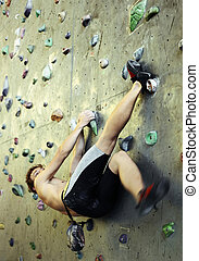 Climbing - Young man climbing on indoor wall. Focus on foot