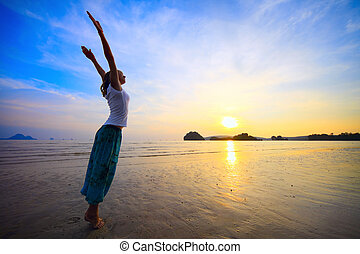 Woman - Young woman with raised hands standing on wet sand...