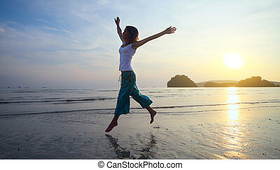 Woman - Young woman with raised hands jumping over wet sand