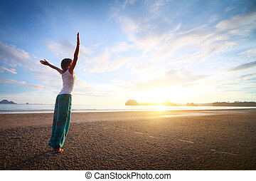 Woman - Young woman with raised hands standing on sand and...