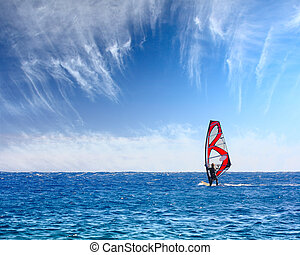 Surfing - Windsurfer with red sail on blue sea