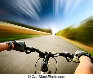 Bike - Rider driving bicycle on an asphalt road. Motion...