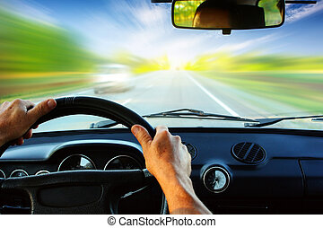 Car - Hands on steering wheel of a car driving on an asphalt...