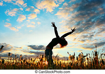 Woman - Young woman with raised hands standing on meadow...