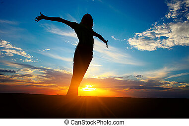 Woman - Young woman with raised hands standing on land over...