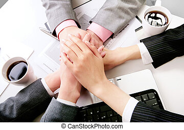 Symbol of partnership - Hands of companions making pile at...