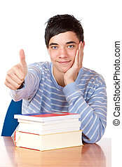 Young happy student sitting on desk with books and shows thumb up