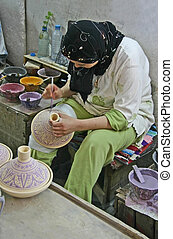 Decorating pottery - Young Moroccon woman busy decorating...