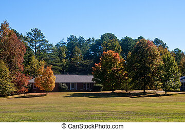Ranch House on Grass Hill in Autumn - A brick ranch house on...