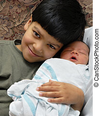 Proud Brother - A young biracial boy proudly hugging his new...