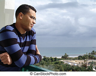 Tunisian man watching the ocean - Tunisian man standing on...