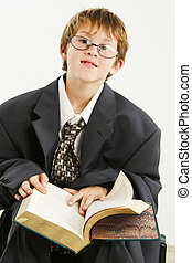 Boy in Baggy Suit Reading - Adorable 7 year old boy in baggy...