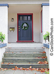 Black door Stucco Home - Maroon bordered black door of beige...