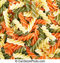 Uncooked italian pasta - three colors spirals as background