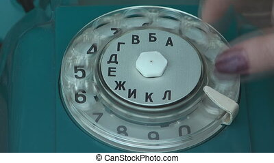 Old telephone - Ladies hand dials the number on the old...