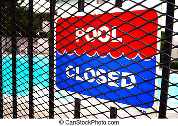 Pool Closed - Pool closed sign on fence outside apartment...