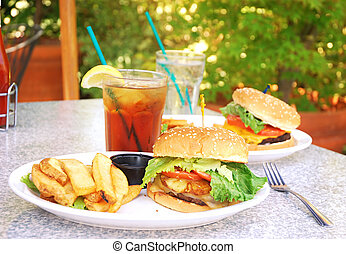 Outdoor Burgers - Two burgers on table at outdoor restaurant