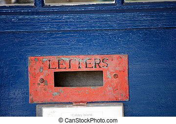 Letter box - A red weathered letter box on a blue door