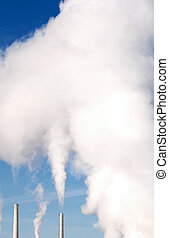 Smoke Stacks - Smoke billowing into deep blue sky from smoke...