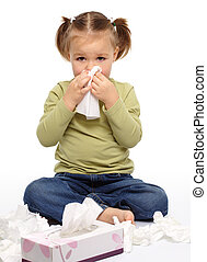 Little girl blows her nose while sitting on floor, isolated...