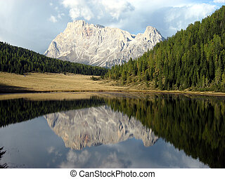 Alpine lake with mountains reflected in water