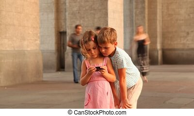 Children are on the square and watching video on smartphone...