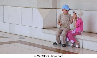 boy and little girl sits near wall