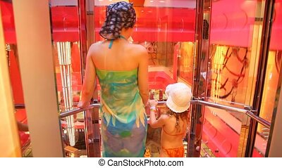 woman and girl in rising up elevator - woman and little girl...