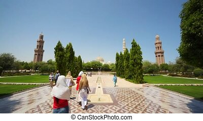 tourists and aborigines walks in park of Muscat - capital of Oman