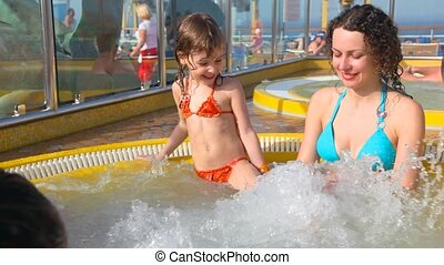 mother and daughter sits in hot whirlpool - happy mother and...